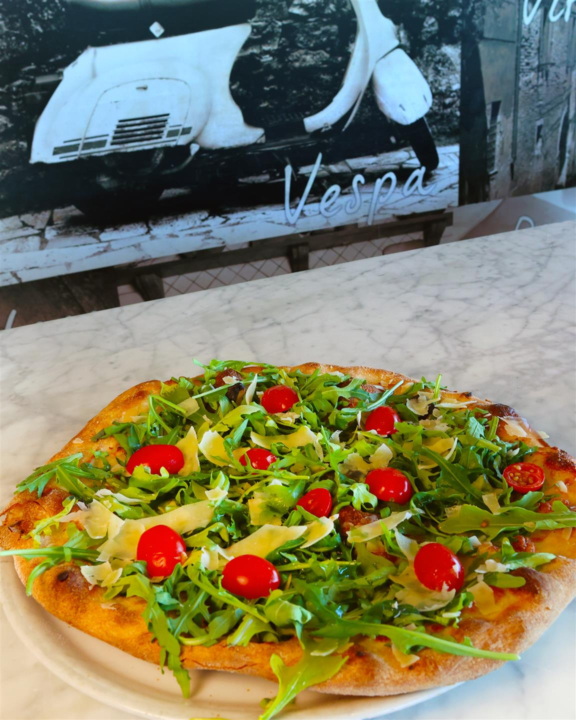 pizza with arugula, shaved cheese, and tomatoes