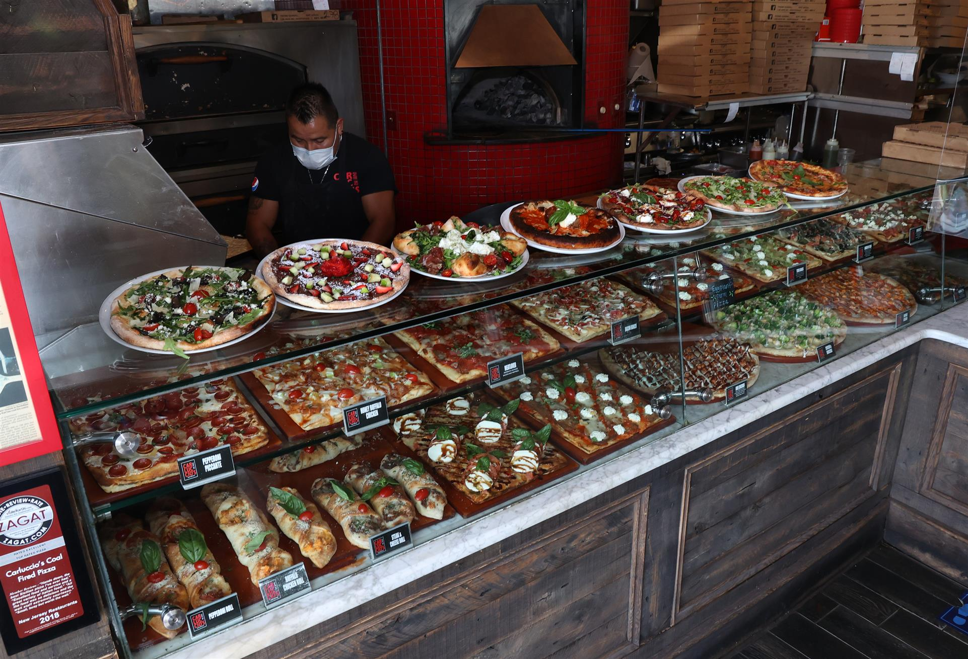 a variety of pizzas and calzones behind a glass window inside the restaurant