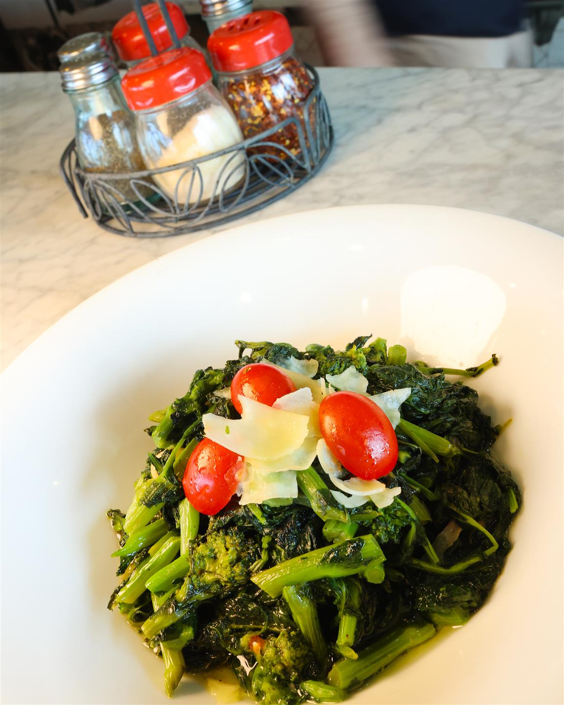broccoli rabe topped with cheese and tomatoes