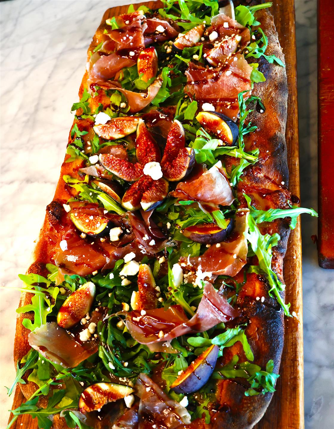 flatbread with arugula, Prosciutto, eggplant, and sprinkled cheese