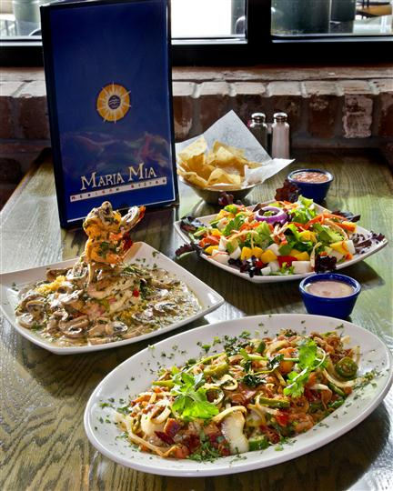 Close up of a table with a variety of Mexican dished laid out and the Maria Mia Mexican Bistro restaurant menu in the background