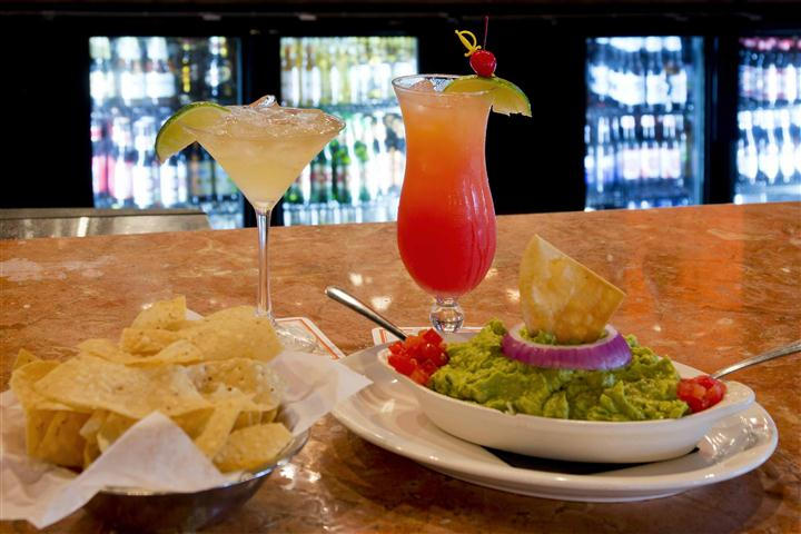 Guacamole salad garnished with an onion ring and diced tomato served with a side of tortilla chips and two cocktail drinks in the background