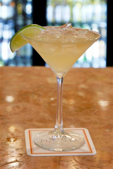 Margarita cocktail with crushed ice and a lime wedge on the rim of a tall glass