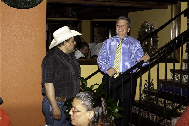 Man in a white cowboy hat talking to a man in a blue shirt and yellow tie at the foot of the stairs