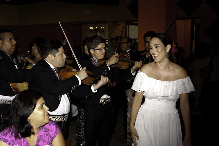 Mexican musicians playing music dressed in traditional costumes and woman in a white dress singing at the front