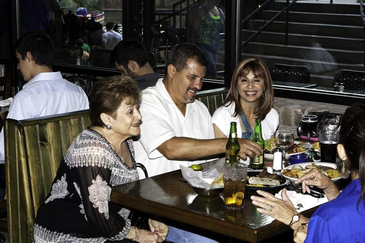 People having dinner in a dining booth and smiling for photo