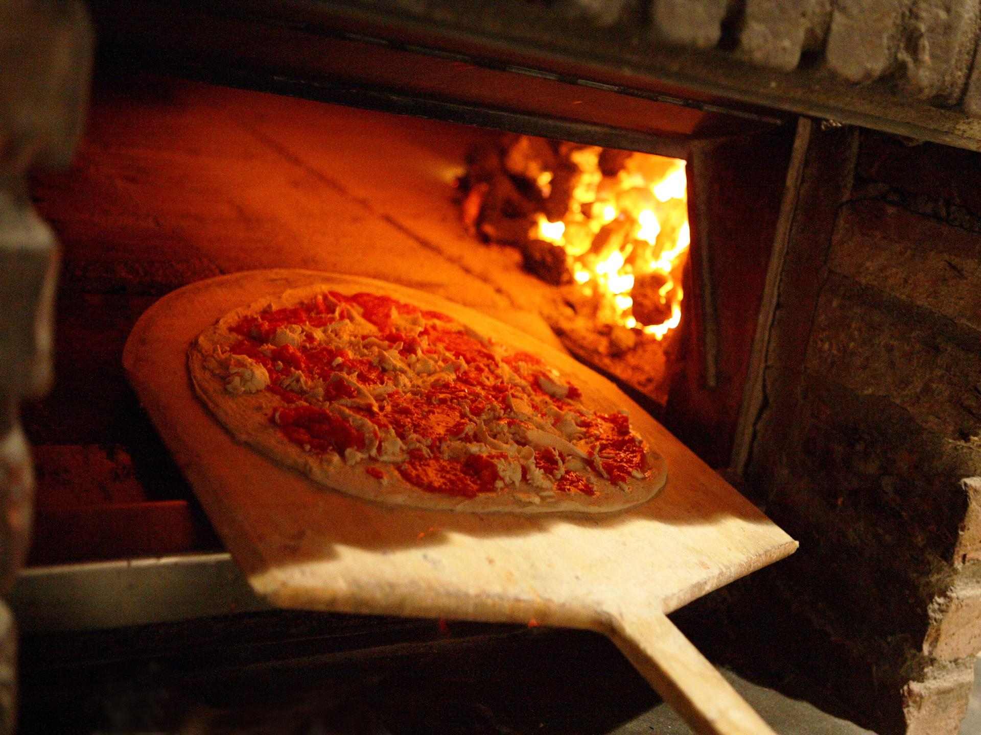 pizza being put into brick oven