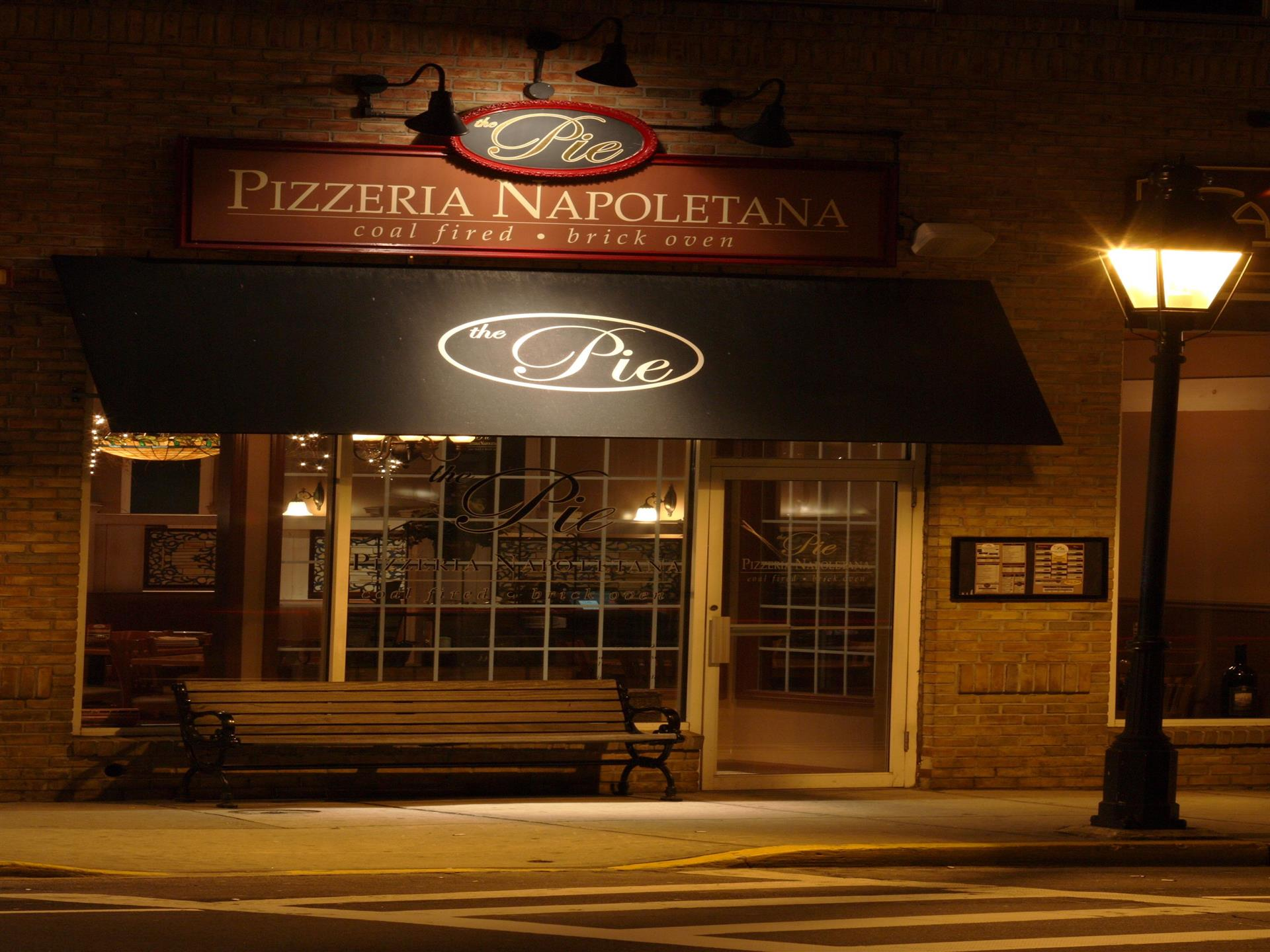 exterior of store front at night with sign reading the pie pizzeria napoletana coal fired brick oven