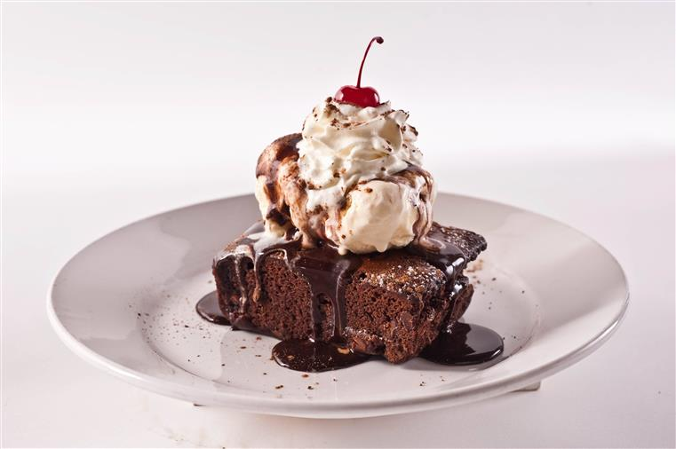 brownie with ice cream and whipped cream on top. a cherry is on top of the whipped cream. brownie is covered in chocolate syrup.