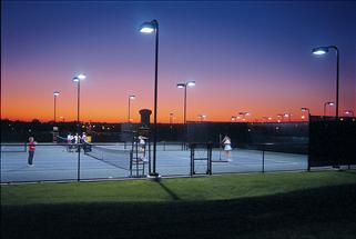 tennis courts at night with talls lights lighting up the court