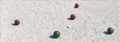 bocce balls laying in the sand