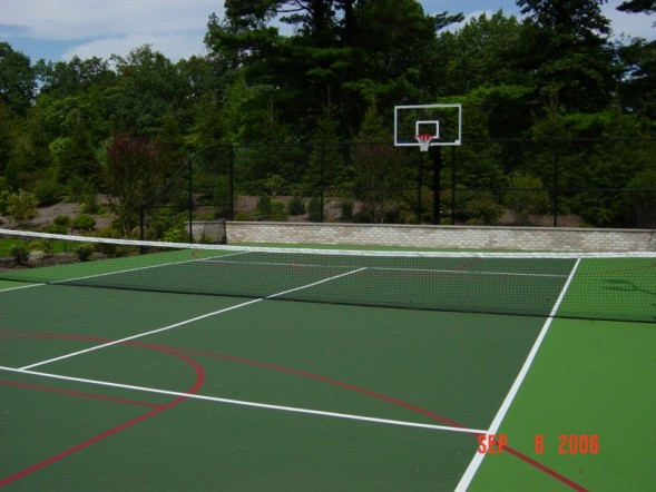 tennis court with a basketball court fenced in surrounded by trees