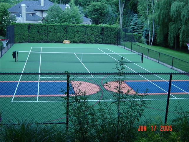 tennis court fenced in surrounded by trees