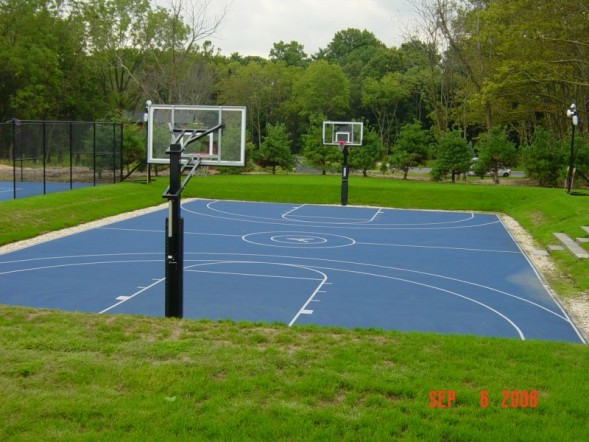 basketball court surrounded by grass and trees