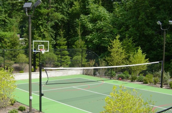 tennis court with a basketball net fenced in surrounded by trees