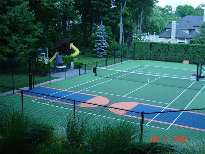 tennis court with a basketball net fenced in surrounded by trees and a small playground