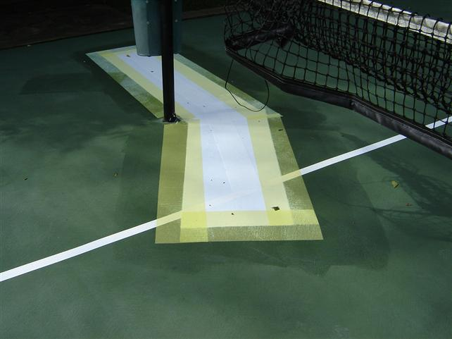tennis court with decorative paint on the floor and a tennis court net