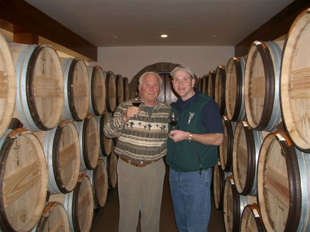 Two men toasting with red wine. In the background are wood barrels.