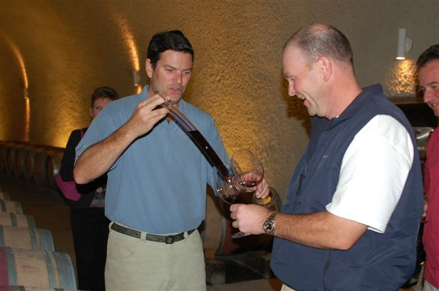 Two men taste testing red wine.