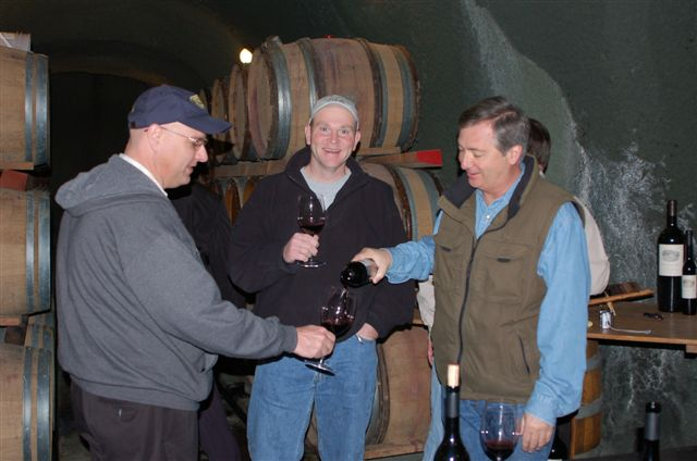 Three men taste testing red wine. In the background are wood barrels.