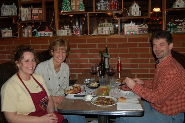 Three members Archie's Friends and Family enjoying dinner in a booth at Archie's Waeside.