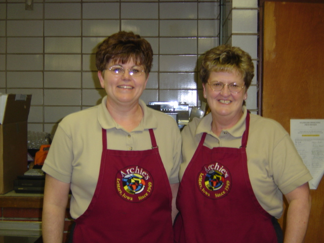 Two staff members wearing aprons smiling.