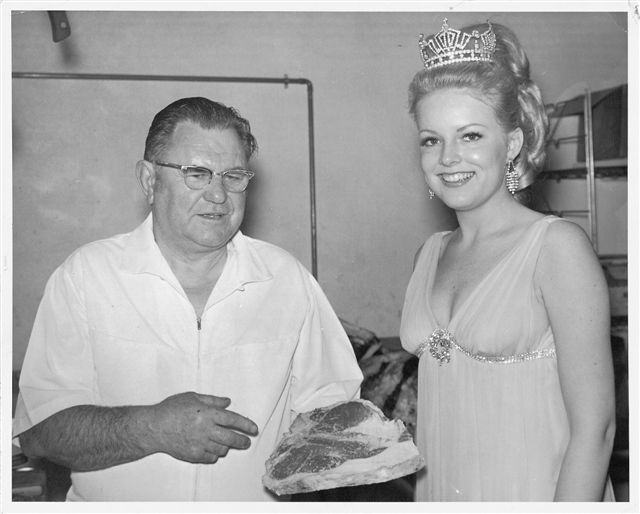 Vintage photo of Archie talking to pageant winner wearing her crown.