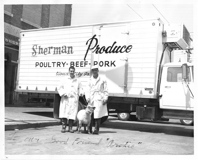 Vintage photo of two staff members in front of a Sherman Produce truck with a goat.