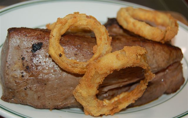 Cooked steak close up with fried onion rings.