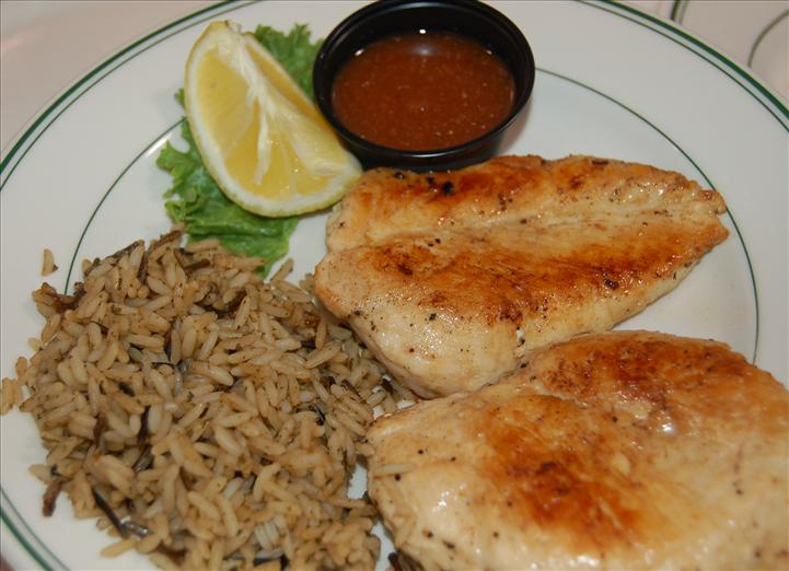 two grilled chicken breasts with a side of rice on a plate.