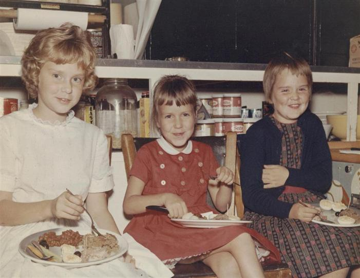 Vintage photo of three children smiling and enjoying a holiday dinner