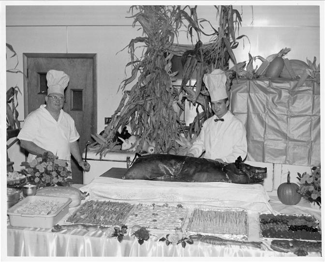 Vintage photo of Archie and restaurant staff preparing a pig roast