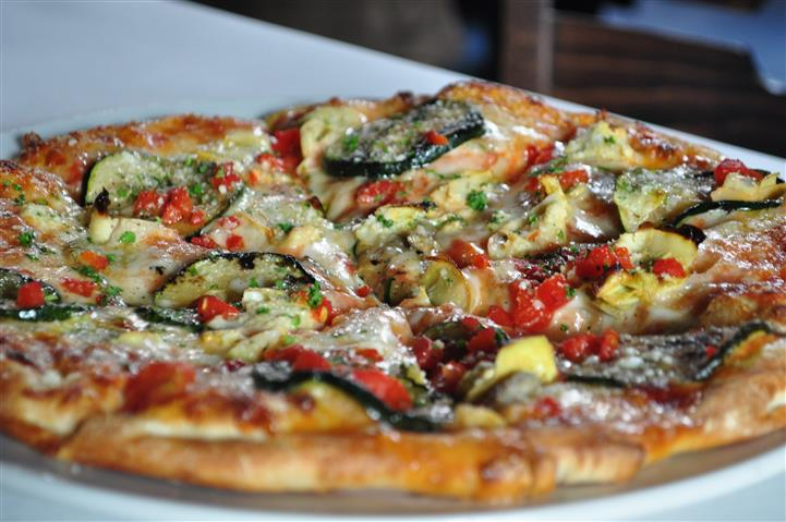 pizza topped with eggplant, peppers and other vegetables
