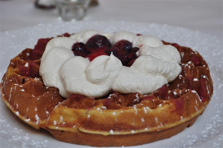 Breakfast waffle with whipped cream topped with berries