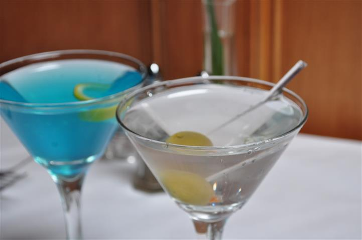Blue drink next to a clear martini with an olive