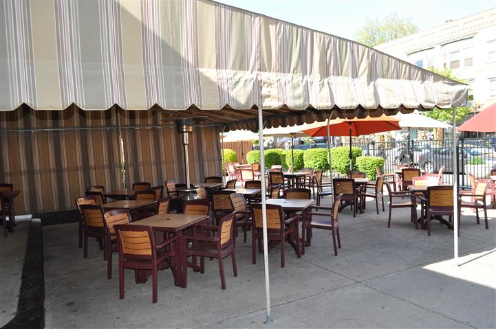 Tables outside with an overhang and green bushes in the background
