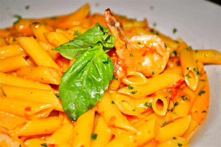 penne pasta with shrimp and basil leaves