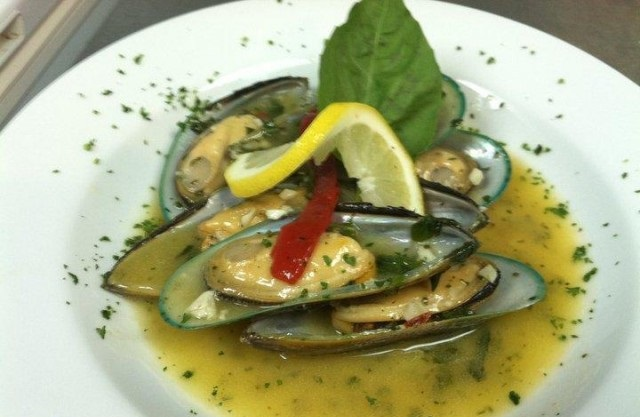 cooked mussels in a bowl with butter sauce and spices