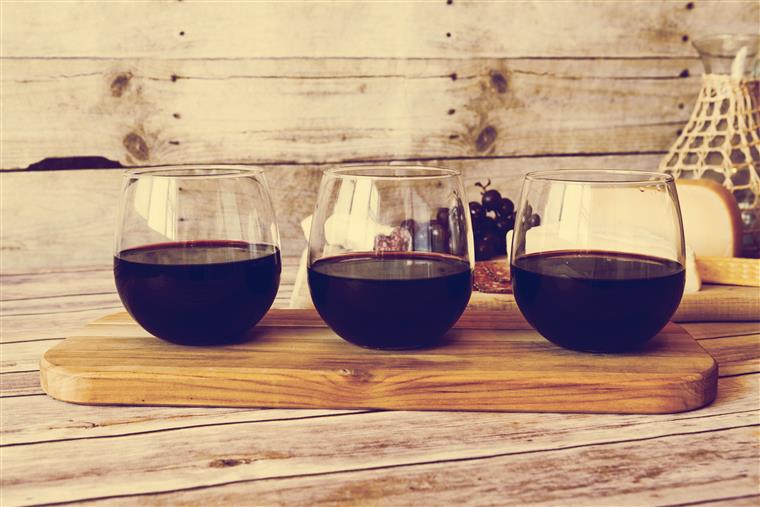 three glasses of wine on a cutting board