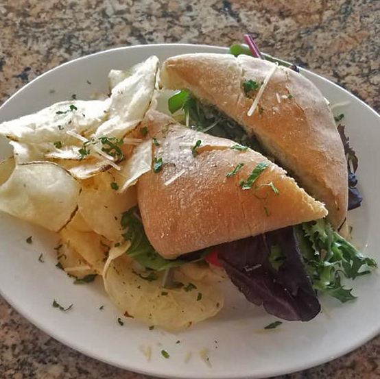 A ciabatta bread sandwich with a side of potato chips
