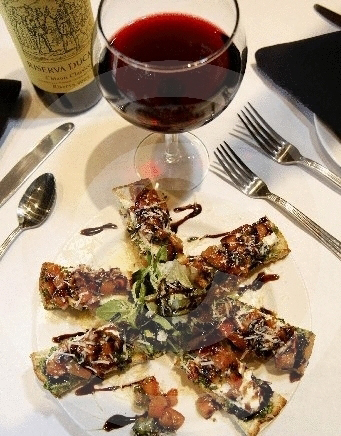 Bruschetta on flatbread appetizer with a balsamic drizzle and a glass of red wine