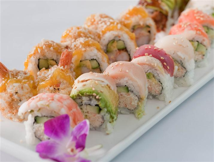 Sushi platter with a plethora different sushi rolls served with a flower garnish