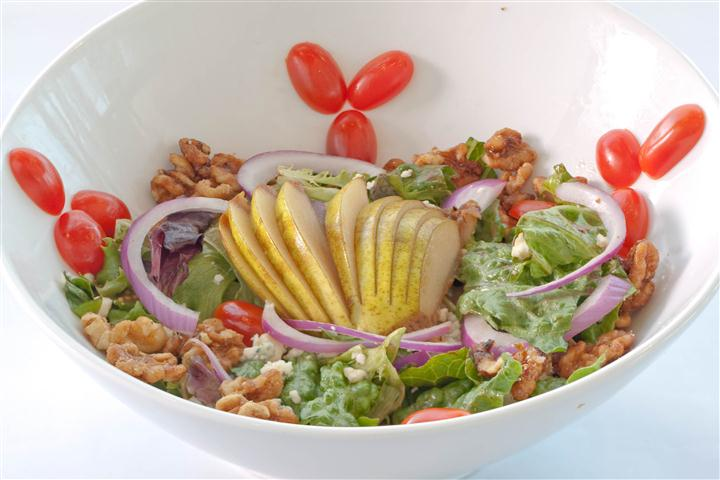 Salad consisting of evenly sliced lemons, lettuce, pecans, and sliced onions