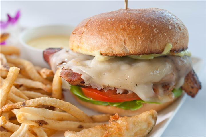 Burger with melted cheese, lettuce, and tomatoes. Served with French fries and dipping sauce