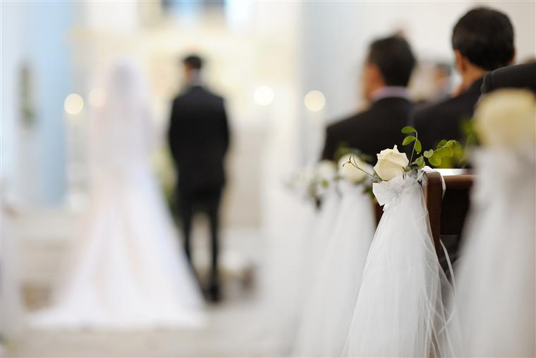 a bride and groom standing at the alter