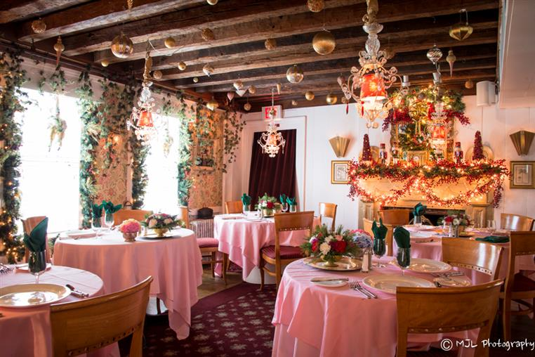 multiple tablecloth tables with flower centerpieces in one room