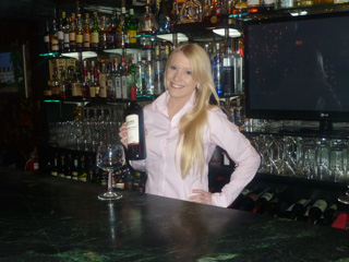 bartender smiling at the camera holding a bottle of wine