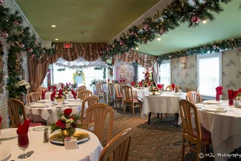 multiple table cloth tables with flower centerpieces and place settings