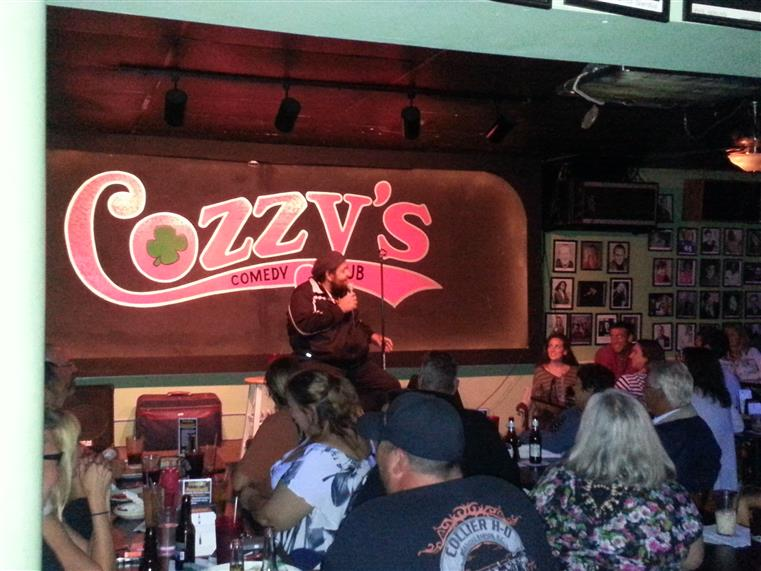 Inside of the comedy club looking at the neon Cozzy's Logo Sign