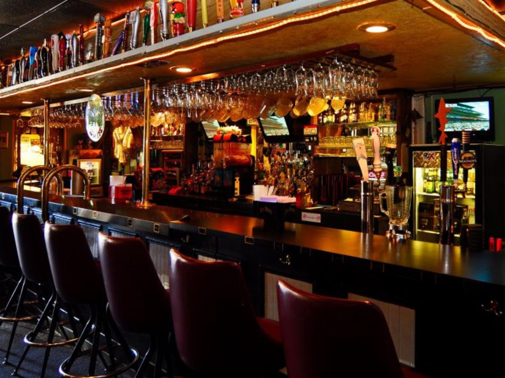 Bar area with chairs set up beside the bar-top with beer taps and glasses hanging from the ceiling